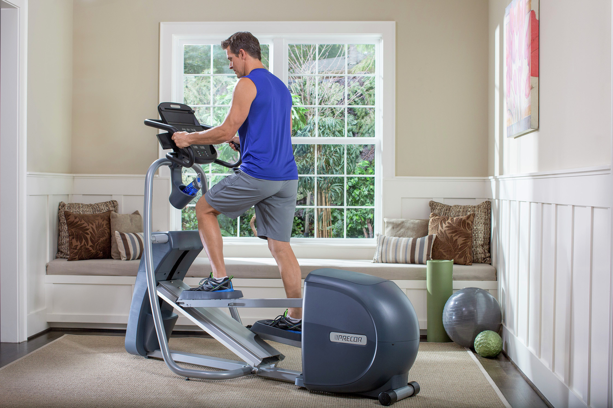 Man doing a workout on Precor elliptical machine at home
