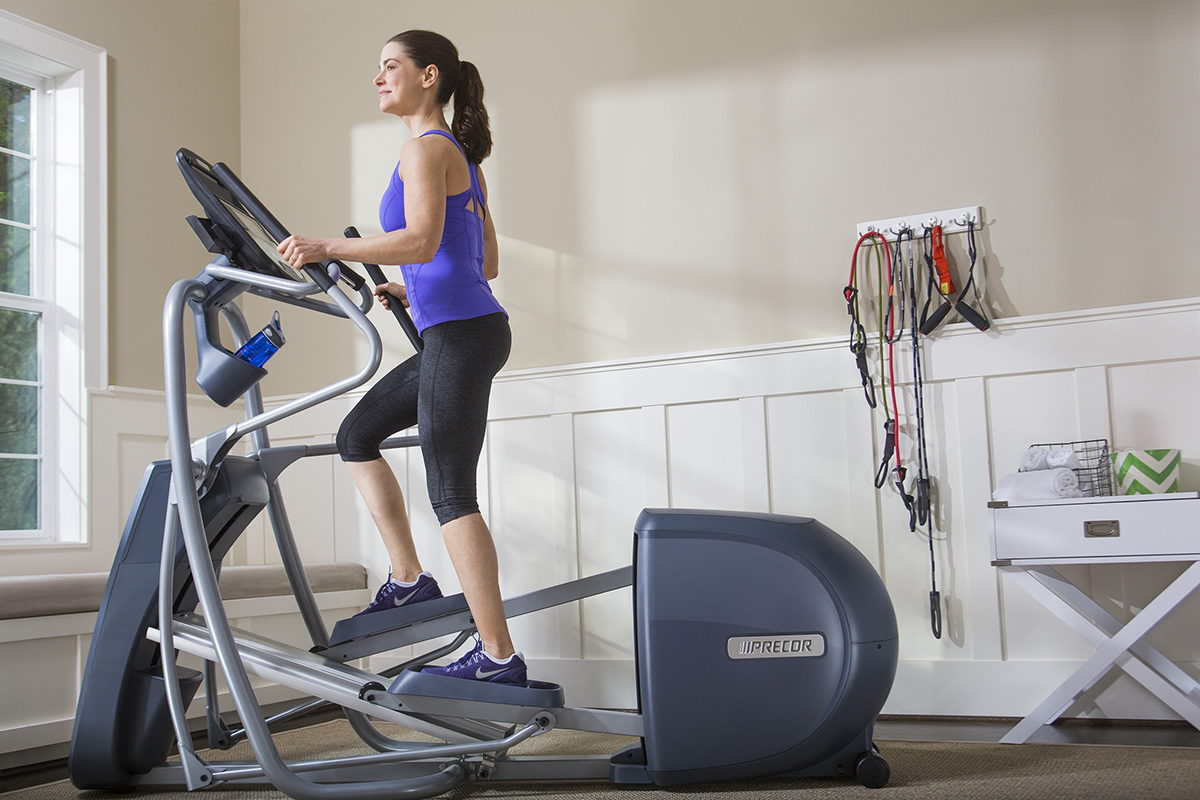 Woman working out at home on a Precor elliptical EFX 427