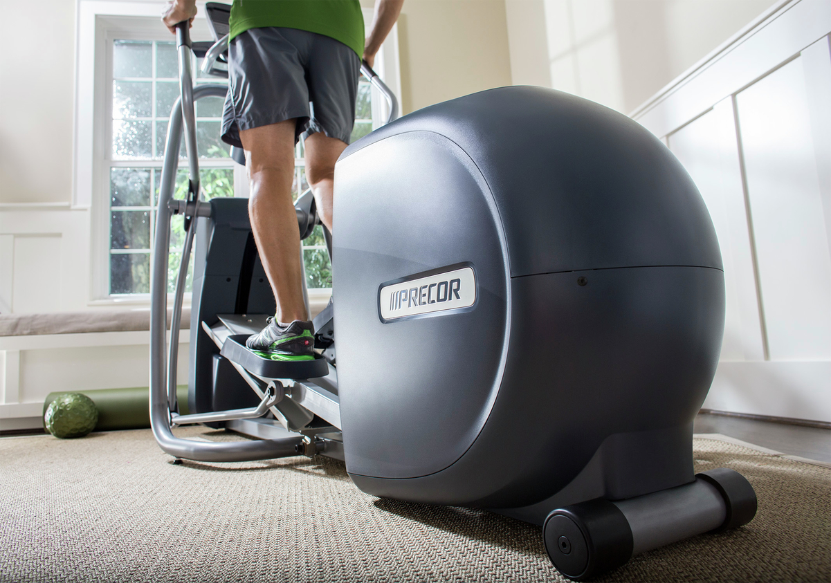 Close-up image of man exercising on an elliptical in his home with a focus on the rear drive and the CrossRamp technology