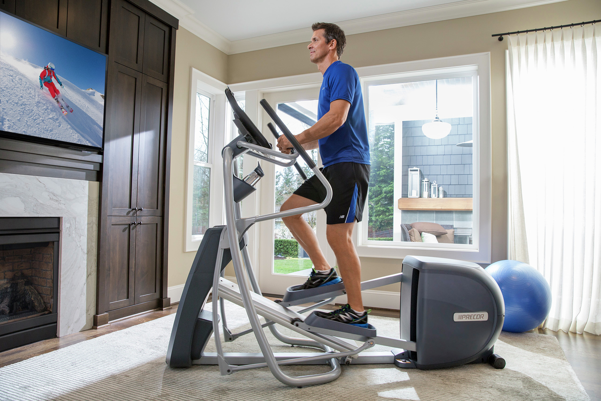 Man working out on a Precor elliptical, EFX 447, while watching TV in his living room