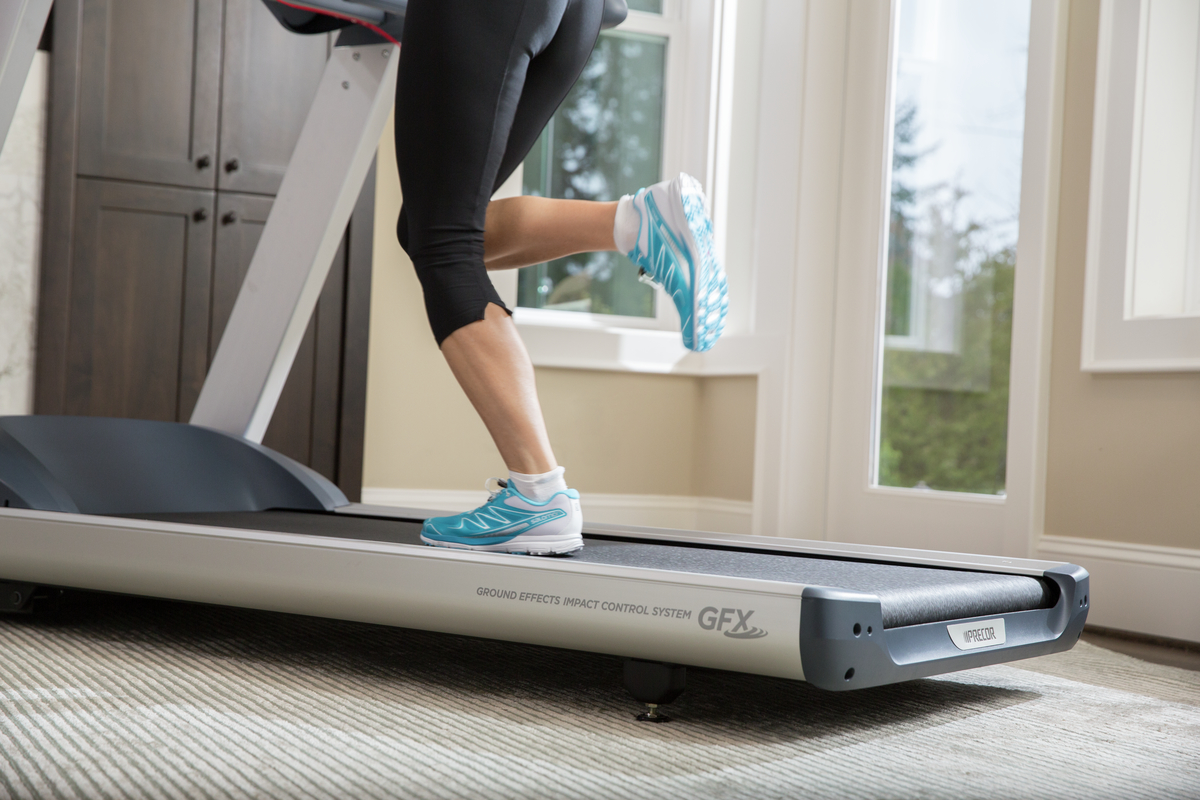 Close up of woman running on a Precor 400 Line treadmill with Ground Effects Impact Control System