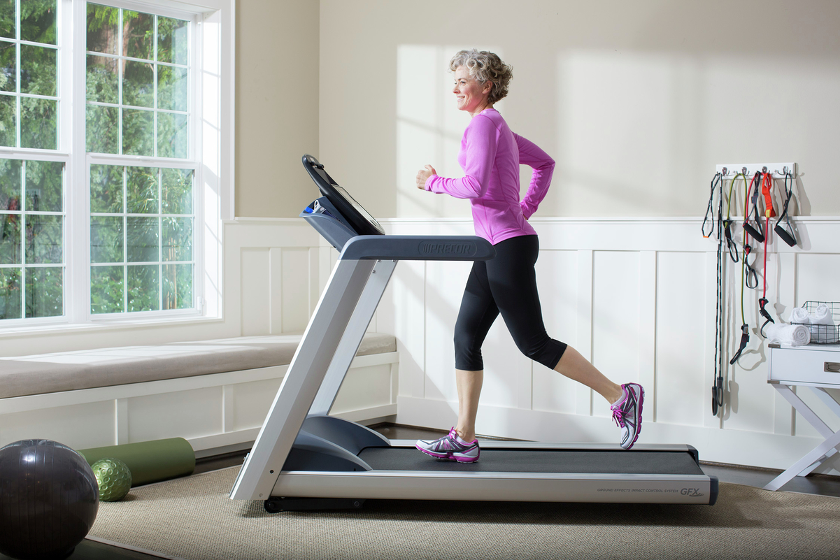 Mature woman runs on a Precor treadmill in her home gym