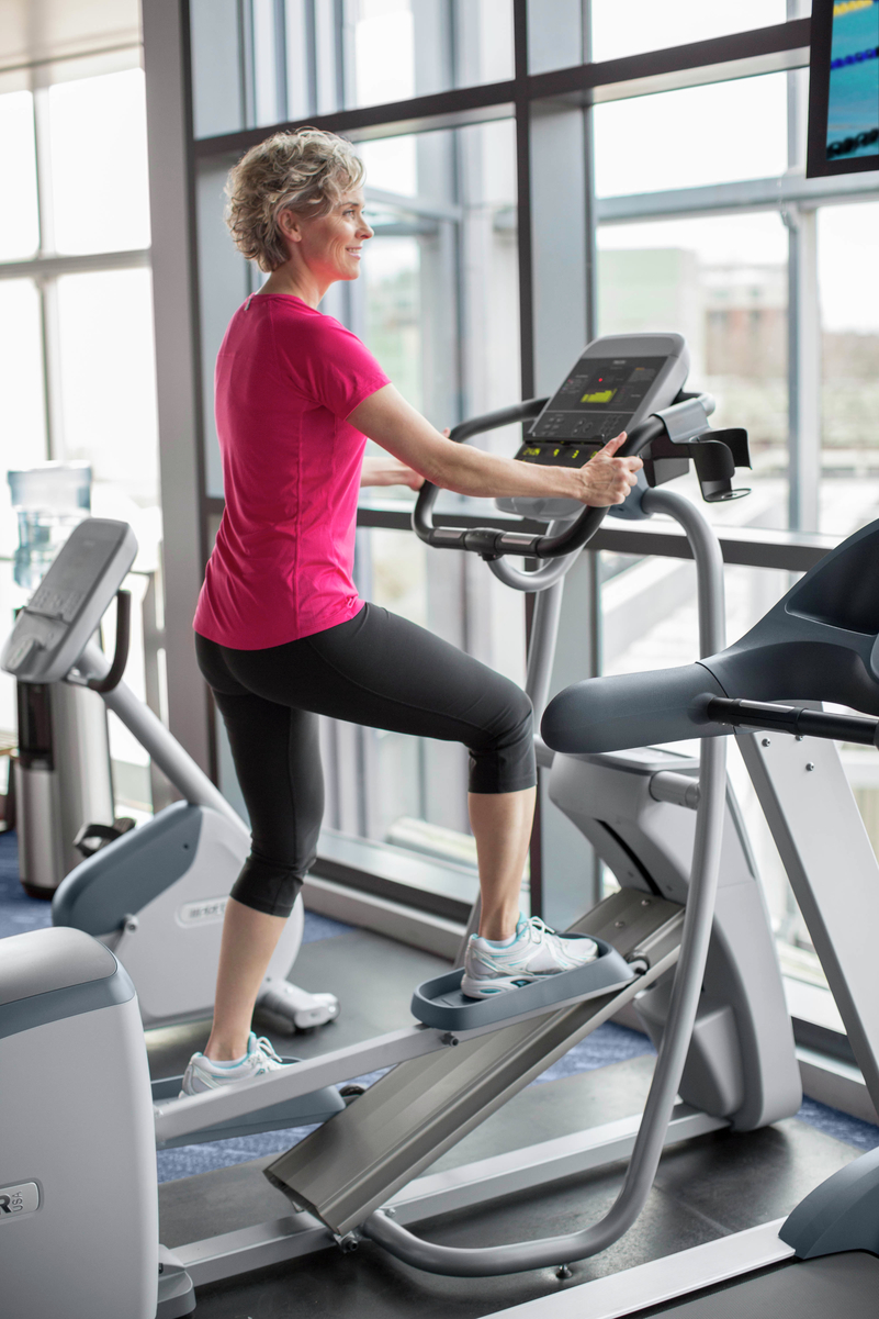 Mature woman working out on a Precor elliptical at a corporate wellness center