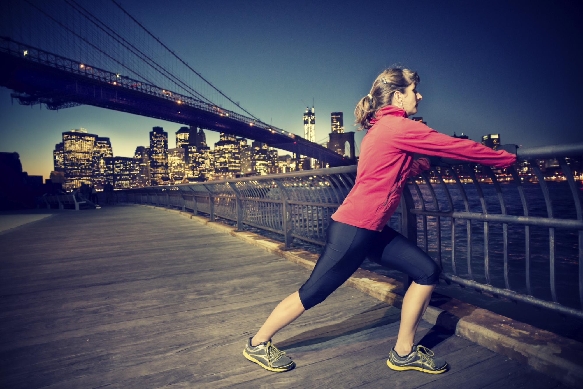 Female exerciser stretching their legs during a workout along the river with a large bridge running across