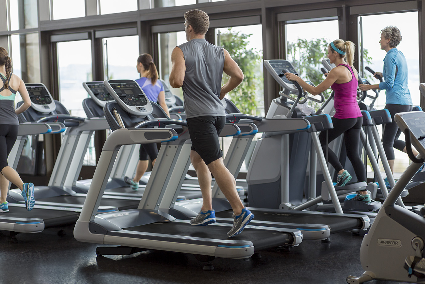 A group of people exercise on Precor TRM 835 treadmills and AMT 835 Adaptive Motion Trainers with P30 consoles at a fitness club.
