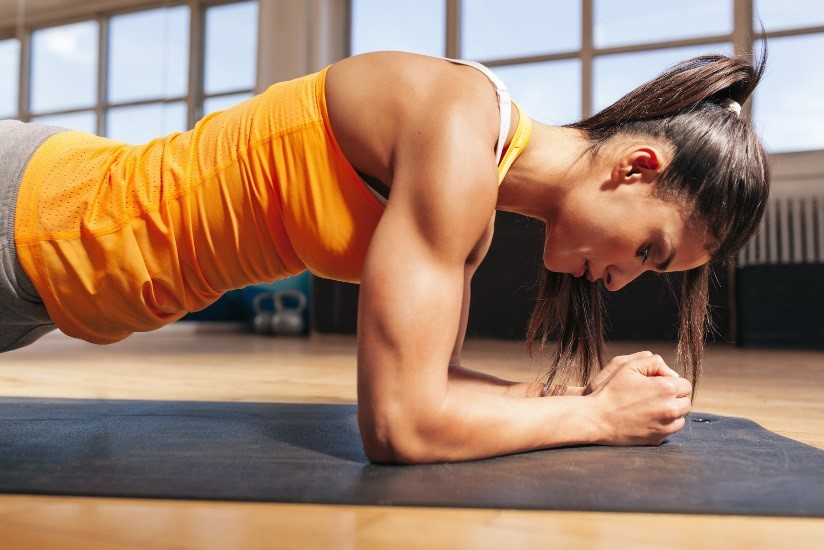 Close-up of a female exerciser doing a forearm plank on a mat in her home gym