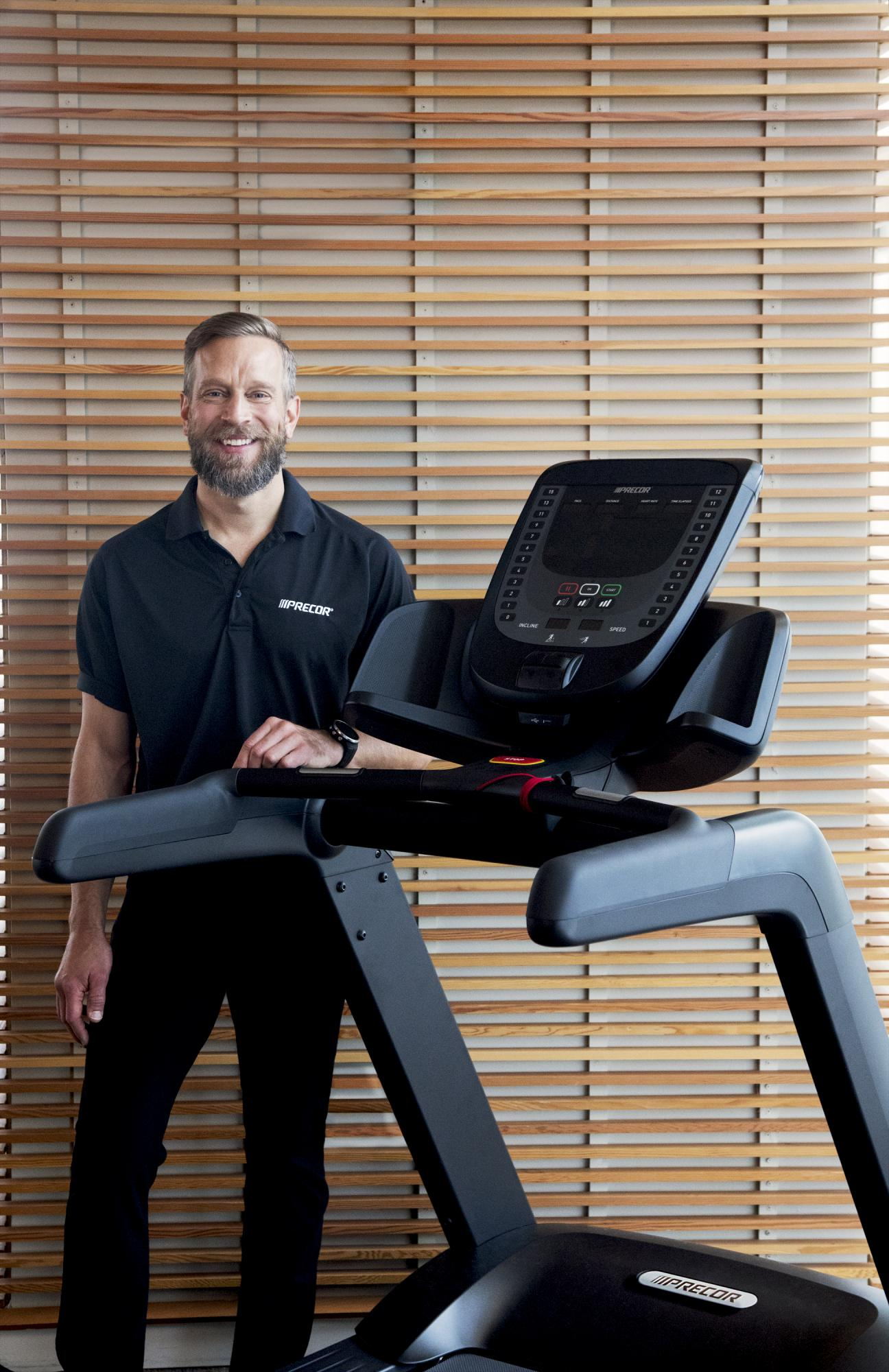 Male Precor customer service representative in front of a Precor TRM 731i interval treadmill with a P31i consoleM 885 treadmills with P80 consoles