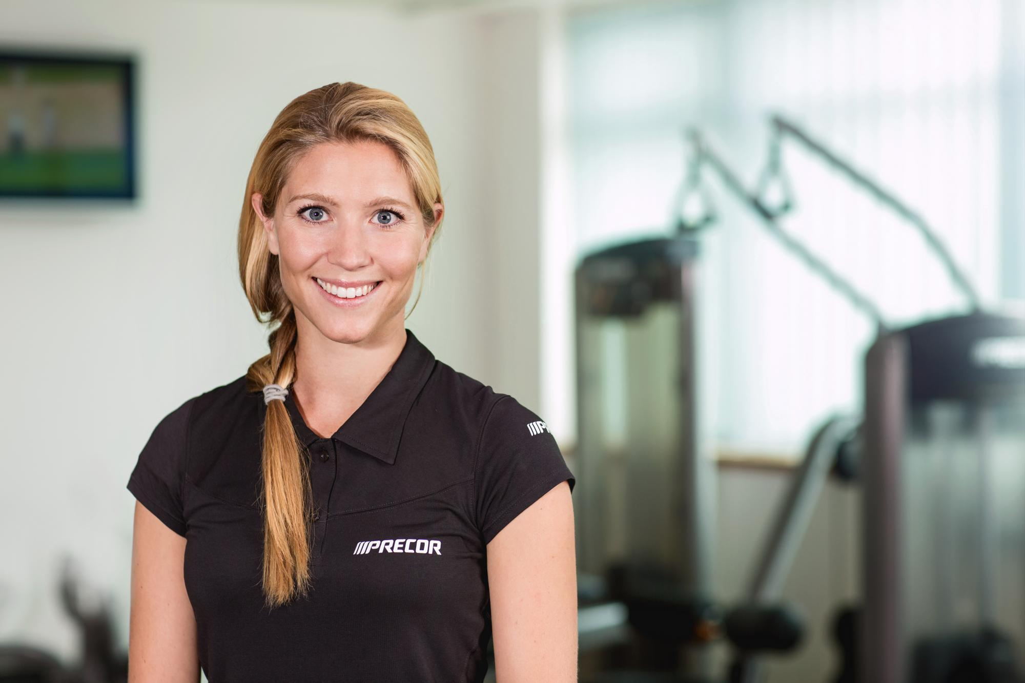 Female Precor sales representative in a customer's home gym 85 treadmills with P80 consoles