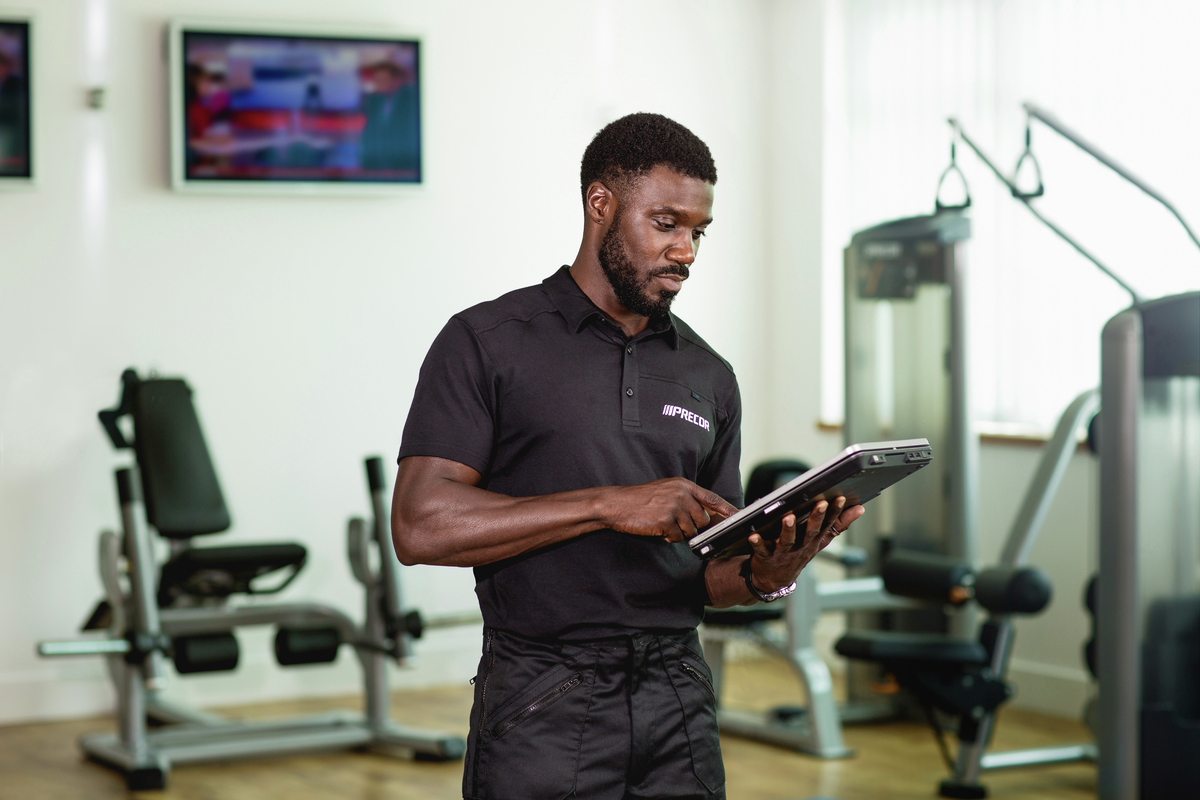 An authorized Precor dealer is working on a tablet at a Precor home gym equipment showroom