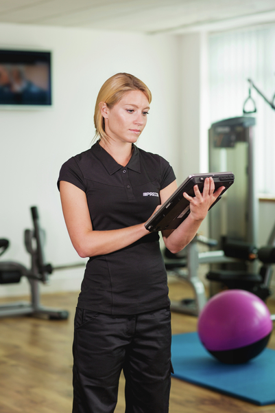 An authorized Precor dealer works on a tablet at a home gym